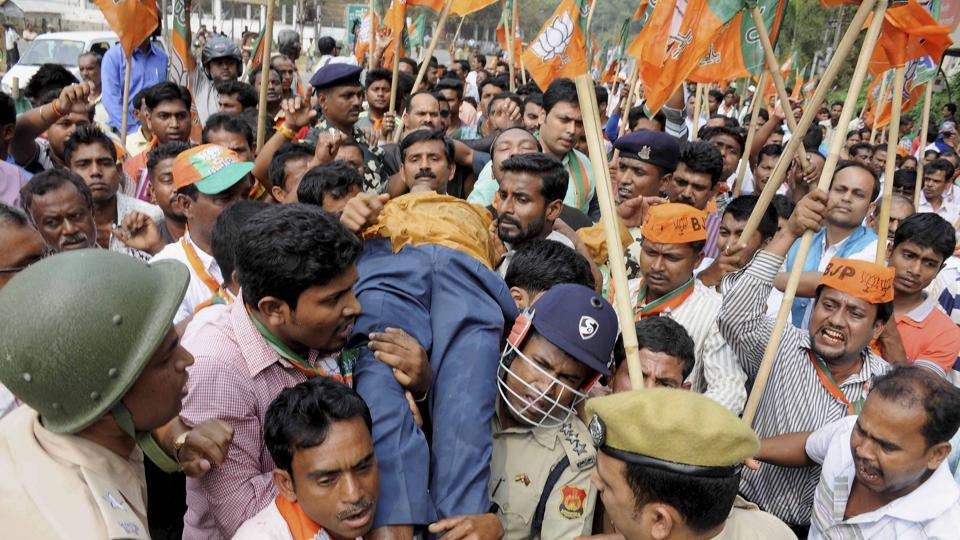 An injured BJP supporter is carried for treatment after police action during a protest rally.