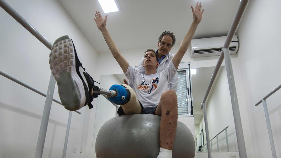 Jakson Follmann, a survivor of a plane crash in Colombia in 2016 in which most of his Chapecoense teammates perished, exercises with his doctor Jose Andre Carvalho during a rehabilitation session at a clinic in Sao Paulo, Brazil.