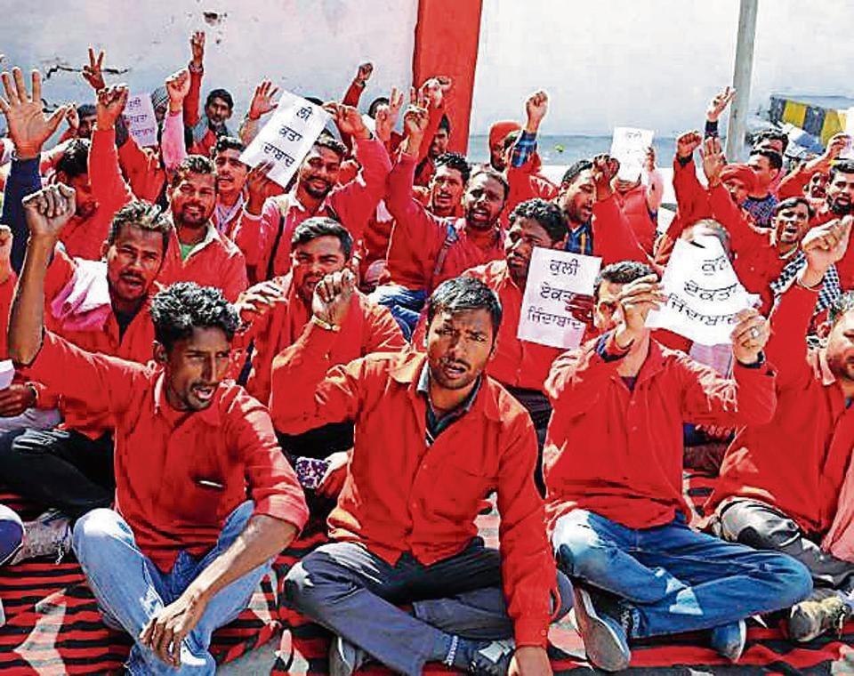 Coolies protesting outside the railway station in Jalandhar on Saturday. Coolies say that the title of 'sahaayak' has not had any positive impact on their lives.