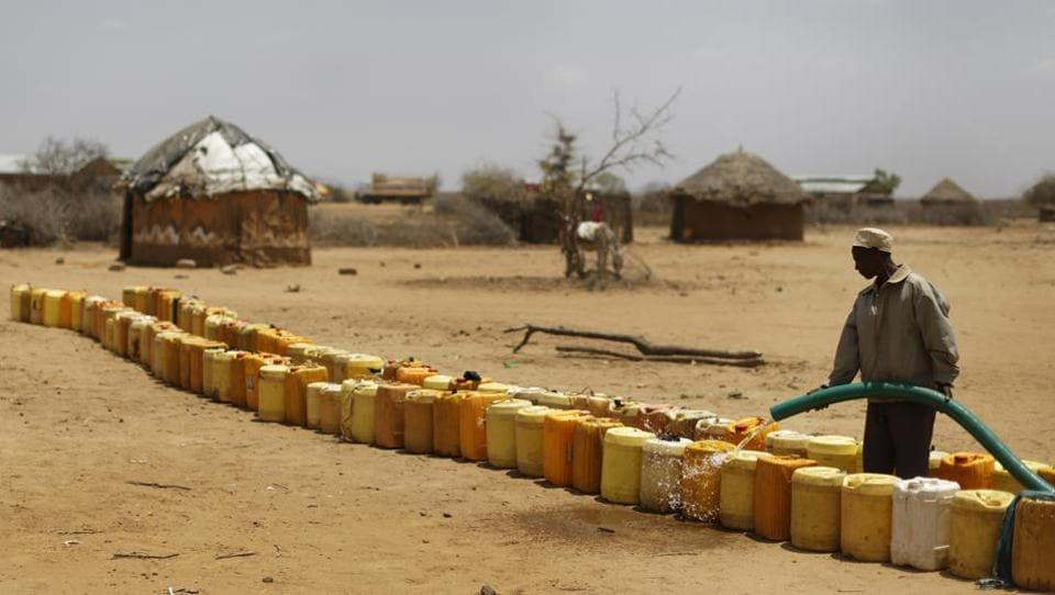 A man fills a long line of plastic water containers from a tanker, in the drought-affected village of Bandarero. (Ben Curtis / AP)