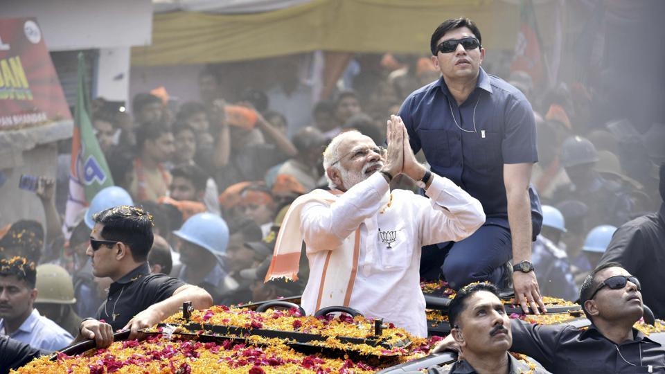 Prime Minister Narendra Modi greets the crowd during the road show. The crucial Varanasi region will go to polls in the seventh and final phase of the Uttar Pradesh election on March 8. (Arun Sharma/HT PHOTO)