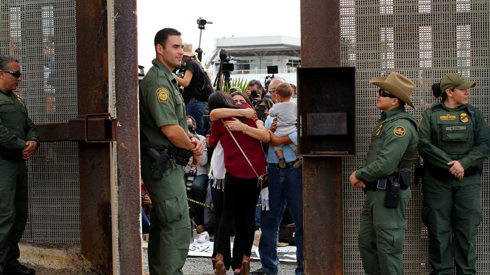 US Border patrol agents stand watch at an open gate on the fence along the Mexico border to allow Delia Valdovinos-Sanchez to embrace Ramona Vargas, as part of Universal Children's Day at the Border Field State Park, California, U.S. on November 19, 2016.
