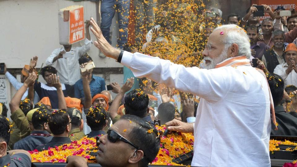 Prime Minister Narendra Modi showered with flower petals during the  roadshow.  (Adarsh Gupta / HT Photo)