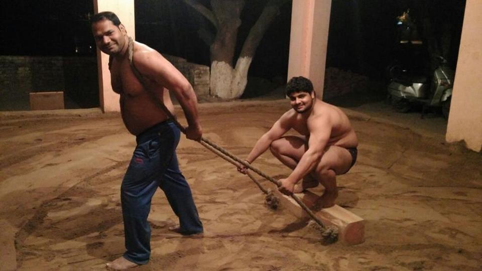 Ashok Pehelwan levels the soil of akhada by pulling a wooden log.