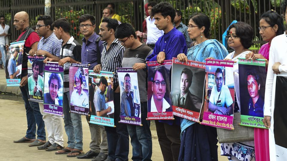Bangladeshi activists hold the photos of activists, writers and bloggers who were murdered by unidentified people in the last few years, in Dhaka, in June 2016.