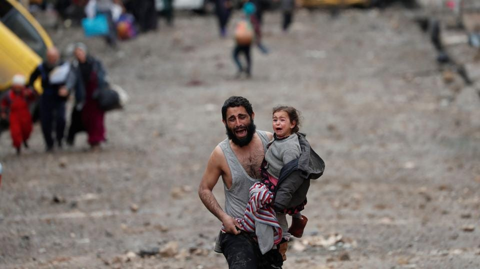 A man cries while carrying his daughter as he walks from Islamic State controlled part of Mosul towards Iraqi special forces soldiers during a battle in Mosul, Iraq. (Goran Tomasevic/REUTERS)