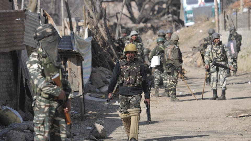 Security personnel stand close to the site of a gunfight in south Kashmir's Tral onSunday.