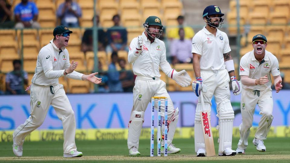 India cricket team skipper Virat Kohli looks on as Australian cricketers celebrate his dismissal.