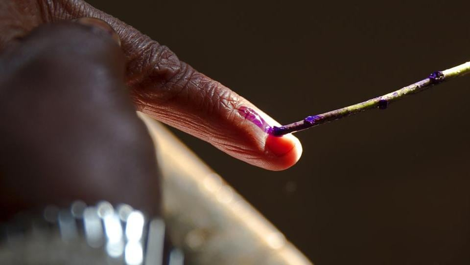 A polling officer marks the finger of a woman with ink before she casts her vote at Muradnagar, in Uttar Pradesh. A model code of conduct is enforced as soon as elections are announced