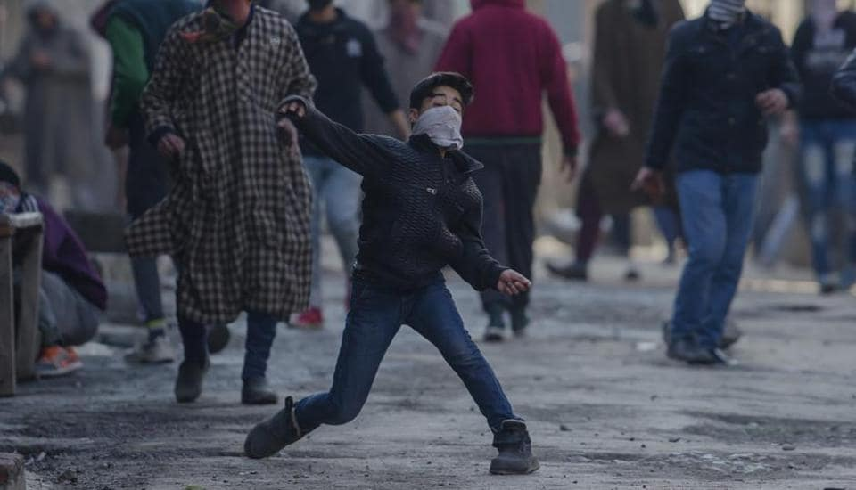 A masked Kashmiri youth throws stones at Indian security forces during a protest in Srinagar,.