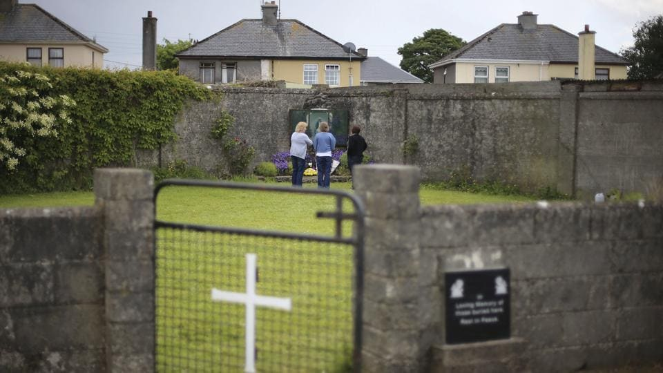 People gather at the site of a mass grave for children who died in the Tuam mother and baby home in Tuam in County Galway.