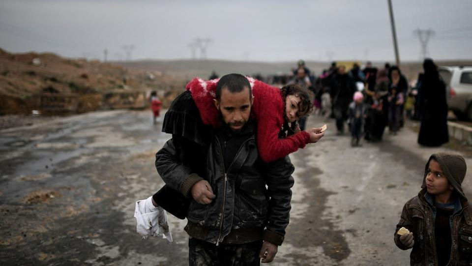 An Iraqi man carries a girl as they walk down a road to flee Mosul. (Aris Messinis/AFP)