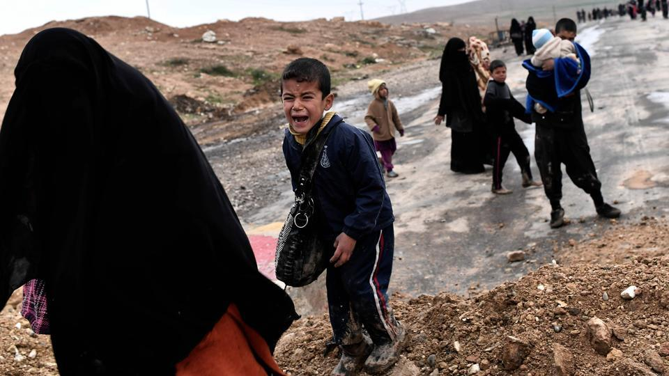 An Iraqi boy cries as families walk down a road while fleeing Mosul. More than 190,000 people are currently displaced as a result of the battle for Mosul, while more fled but have since returned to their homes, according to the International Organisation for Migration. (Aris Messinis/AFP)