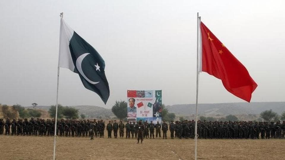Pakistan and China's national flags fly in the foreground as soldiers from both countries stand together for a group shot after holding joint military exercises in Jhelum, located in Pakistan's Punjab province.