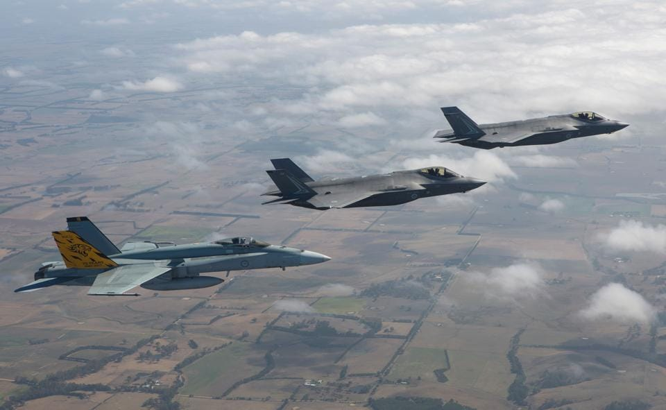 The Royal Australian Air Forces first F-35A Lightening II aircraft, 01 and 02 (C&R) flying in formation with No 2 Operational Conversion Unit F/A-18A Hornet (L) in transit to the Australian International Airshow at Avalon airport in Victoria. (Craig BARRETT / AFP)