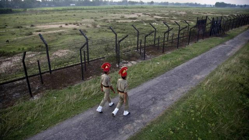 Border Security Force personnel patrol near a fence on the India- Bangladesh border at Thakuranbari village, in Assam.