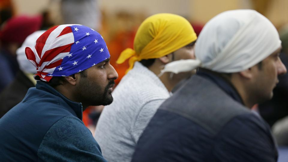 A man wears a head covering with the stars and stripes of a U.S. flag as he attends Sunday services at the Gurudwara Singh Sabha of Washington, a Sikh temple in Renton, Wash., Sunday, March 5, 2017, south of Seattle. Authorities said a Sikh man said a gunman shot him in his arm Friday, March 3, 2017, as he worked on his car in the driveway and told him