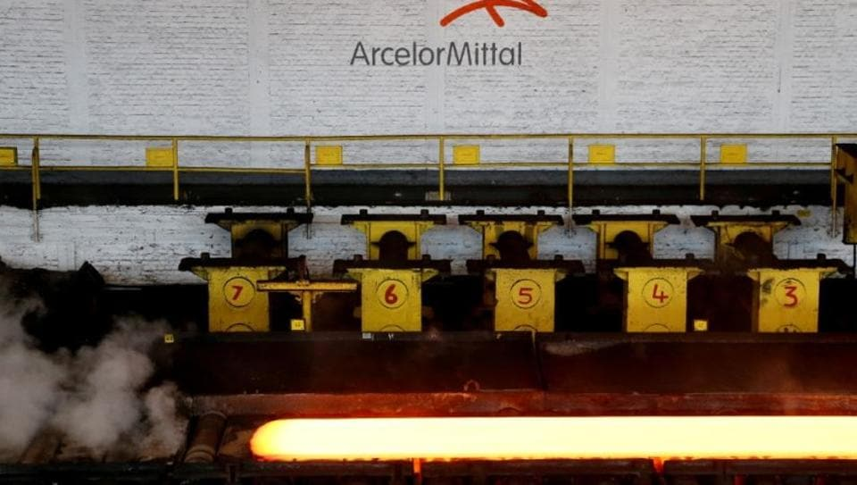 A red-hot steel plate passes through a press at the ArcelorMittal steel plant in Ghent, Belgium.