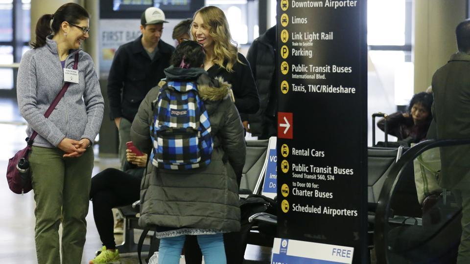 Volunteer law students talk to a traveller at an information station in Seattle-Tacoma International Airport. Airport officials and civil rights lawyers around the country are getting ready for President Donald Trump's new travel ban, which is expected to be released as soon as Wednesday.