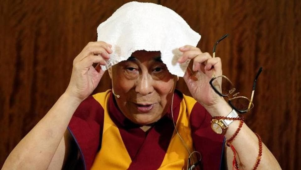 Tibet's exiled spiritual leader the Dalai Lama puts a towel on his head during a news conference in Paris, France, September 13, 2016.
