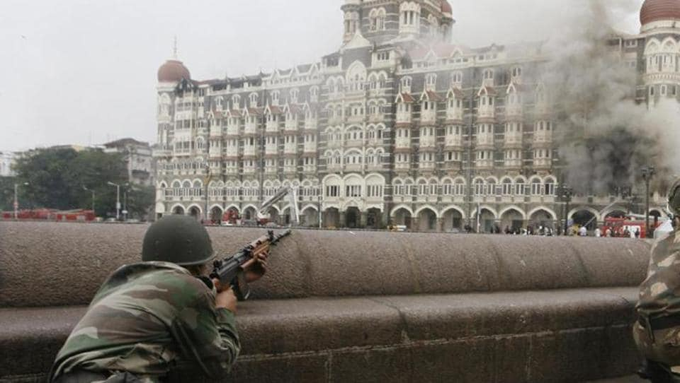Soldiers take up position during a gun battle at the Taj Mahal hotel (seen in the background) in Mumbai in this November 29, 2008 file photo.