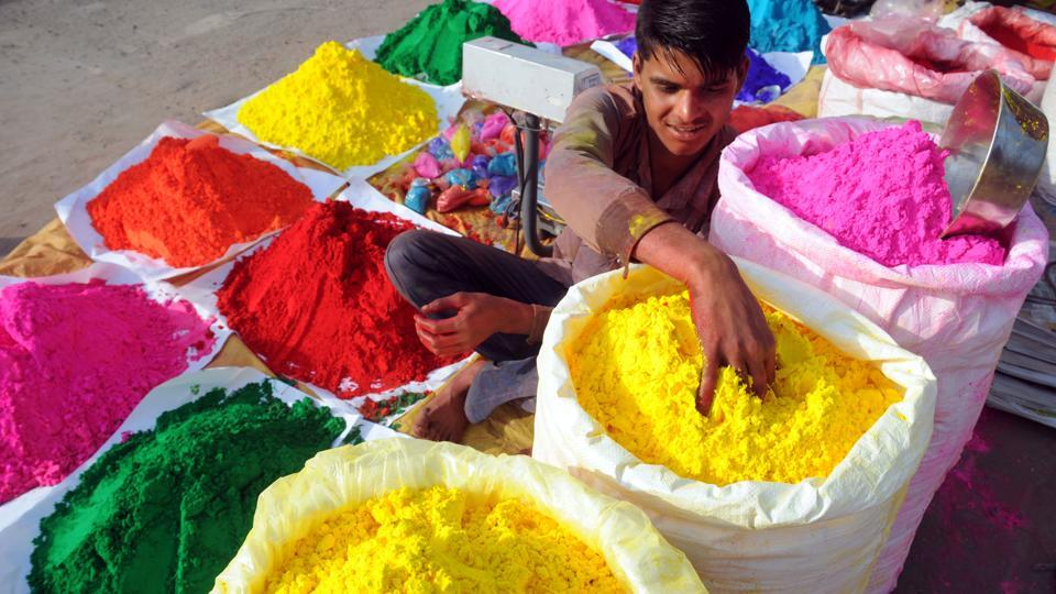 A boy selling colours at a stall waits for customers by a roadside in Gurgaon ahead of Holi.