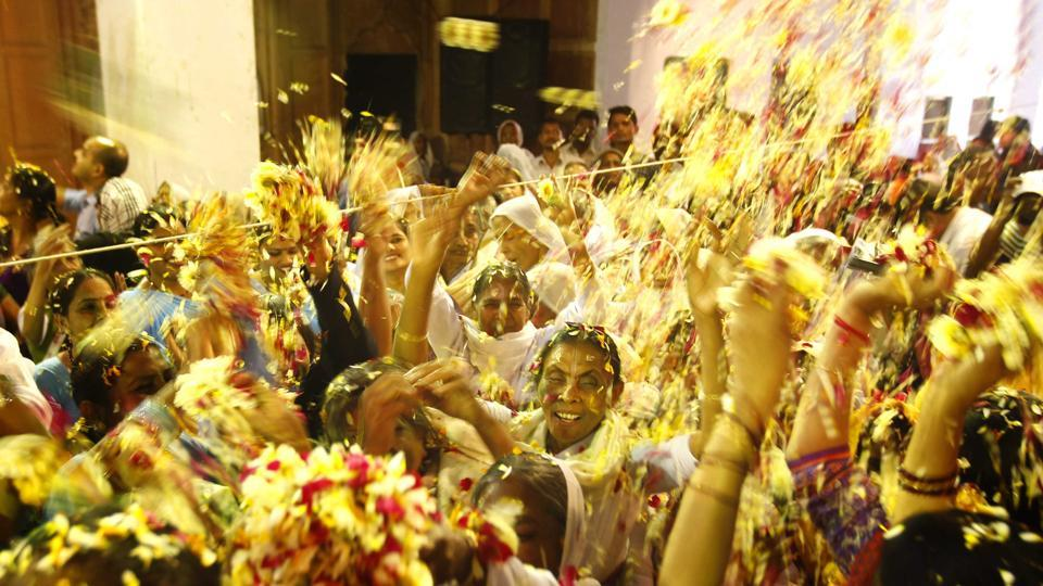Hindu widows throw flower petals at each other as part of Holi celebrations organized by a NGO at Meera Sahbhagini Ashram in Vrindavan. (AJAY AGGARWAL/HT PHOTO)
