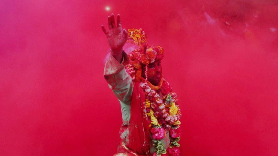 A devotee takes part in rituals on Laddu Holi at Radha Rani temple in Barsana, Uttar Pradesh on Sunday. (PTI)
