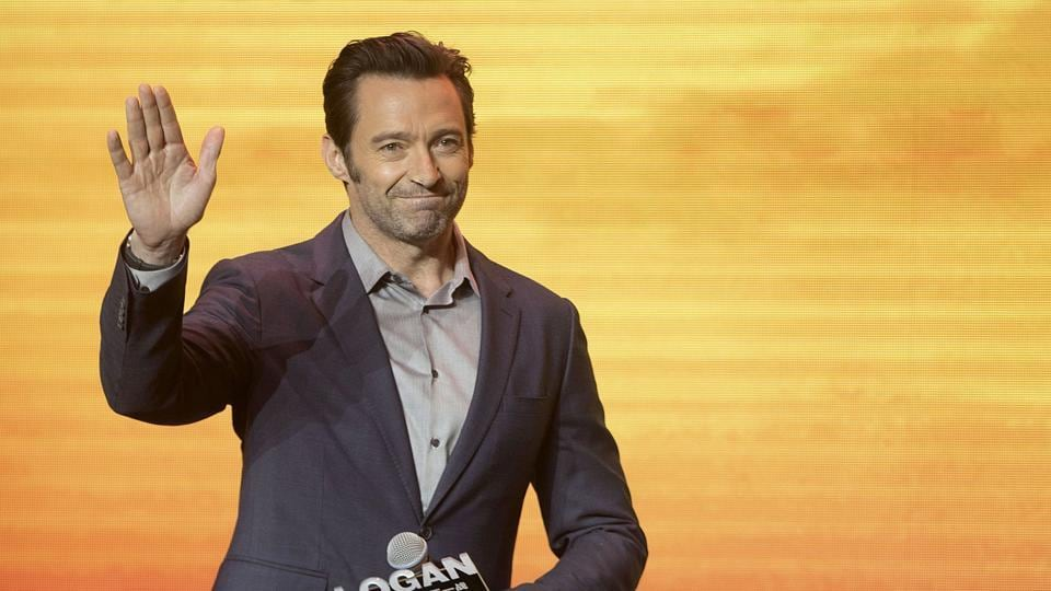 Actor Hugh Jackman waves as he arrives for a press conference for the movie