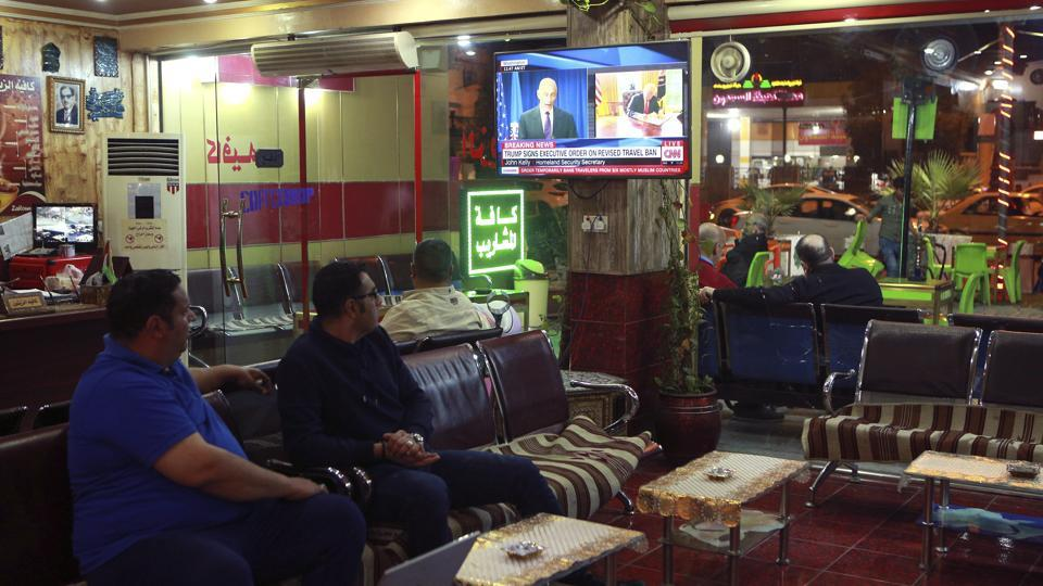 Men at a cafe in Baghdad watch the news on Iraq being removed from the US travel ban.