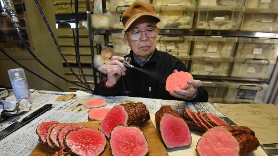 Noriyuki Mishima, a craftsman at Fake Food Hatanaka, spraying paint on a plastic food replica that restaurants across Japan put in their display windows to lure hungry crowds, at the company's studio in Tokorozawa, a suburb of Tokyo.