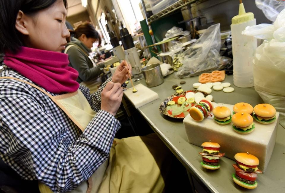 A craftswoman of Fake Food Hatanaka making plastic hamburger earrings at the company's studio in Tokorozawa.  (TORU YAMANAKA  / AFP)