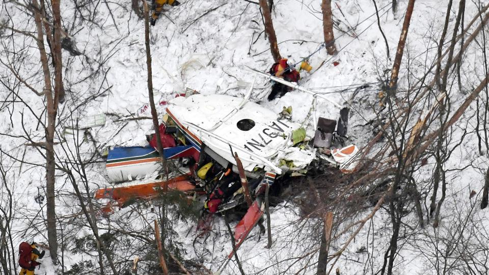 Rescuers work near the helicopter crashed in mountains in Nagano prefecture, central Japan Sunday, March 5.