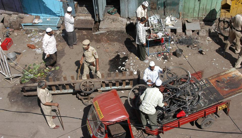 Local and police officers clear debris at a blast site in Malegaon.