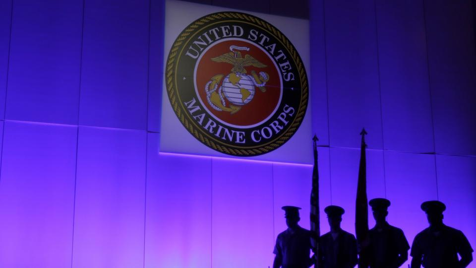 A US Marine Corps Color Guard sands under a Marine Corps emblem in Jupiter, Florida.
