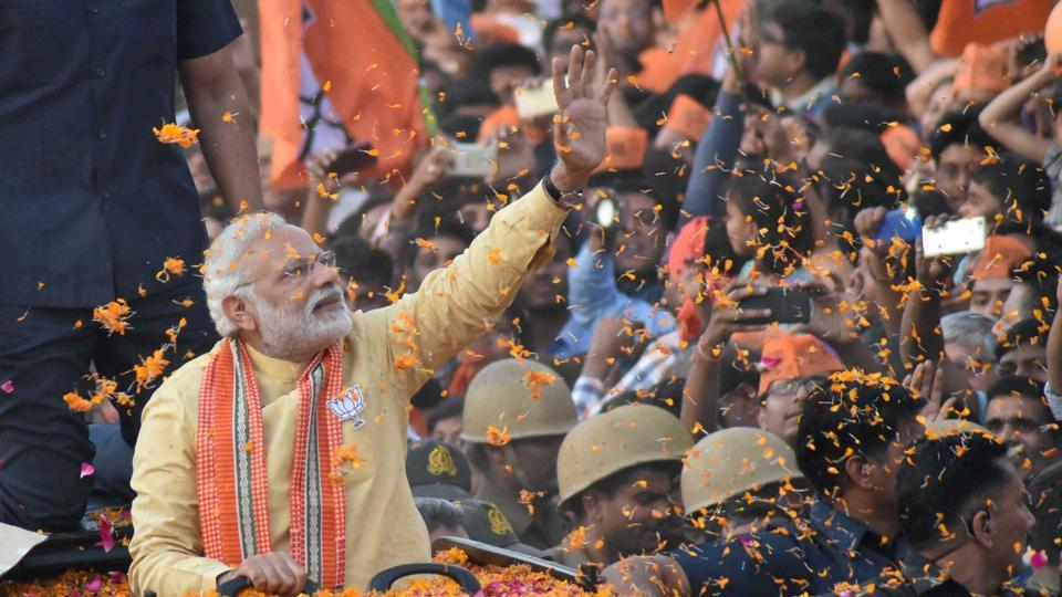 Prime Minister Narendra Modi waves to people during his roadshow in Varanasi on Sunday.