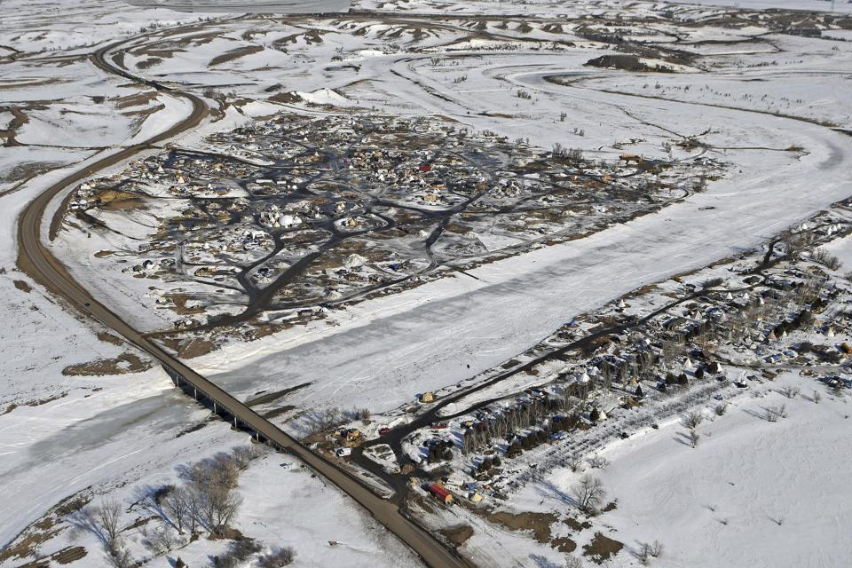 This aerial photo shows North Dakota Highway 1806, at left, where it crosses Cannonball River and Dakota Access pipeline protest camps on both sides of the river Monday, Feb. 13, 2017, in Cannon Ball, N.D. A federal judge on Monday refused to stop construction on the last stretch of the Dakota Access pipeline, which is progressing much faster than expected. It's the last big section of the $3.8 billion pipeline, which would carry oil from North Dakota to Illinois.