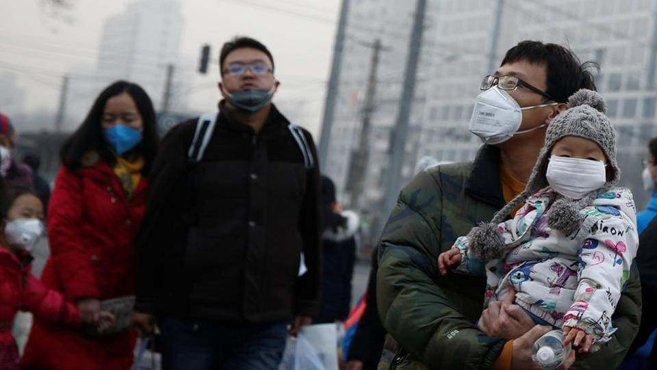 People, including kids, wear face masks as they cross a street on a polluted day in Beijing on January 4.