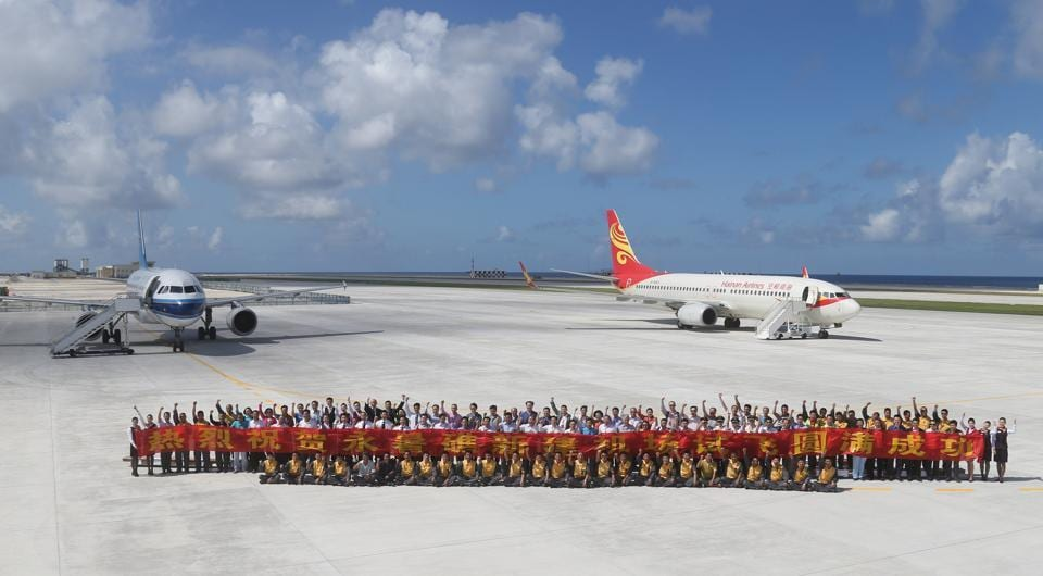 A file photo released by China's Xinhua News Agency shows people posing for a group photo after landing at the airfield on Fiery Cross Reef in the Spratly Islands.
