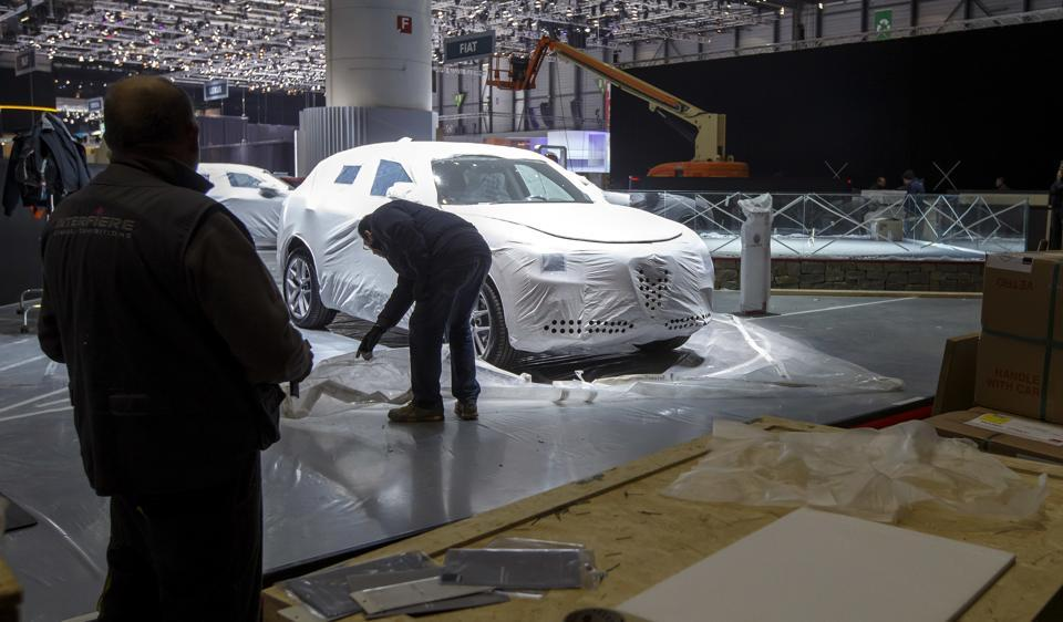 A technician of the Alfa Romeo booth removes a floor protection, during the last preparation prior to the opening of the preview day at the 87th Geneva International Motor Show in Geneva, Switzerland on Sunday.