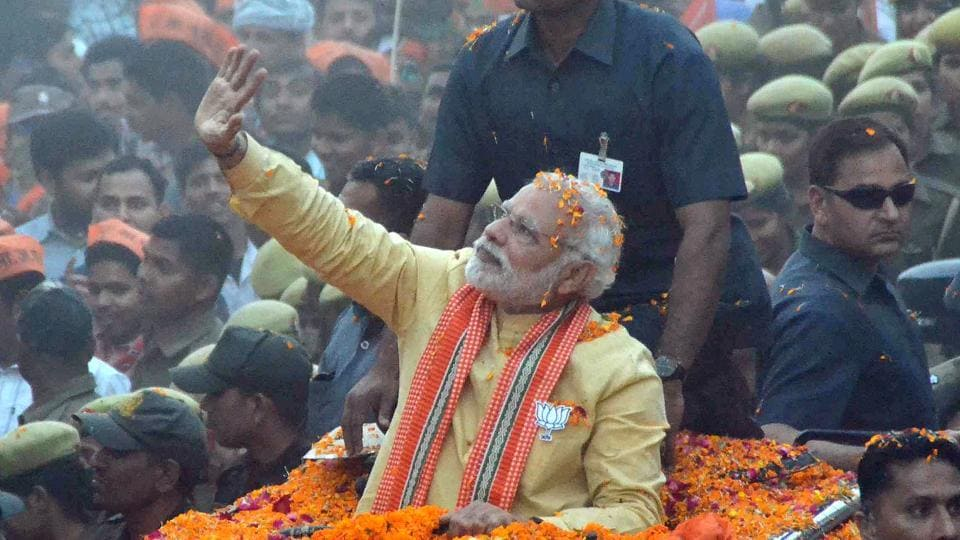 Prime Minister Narendra Modi waves to people during his road show in Varanasi on March 5.