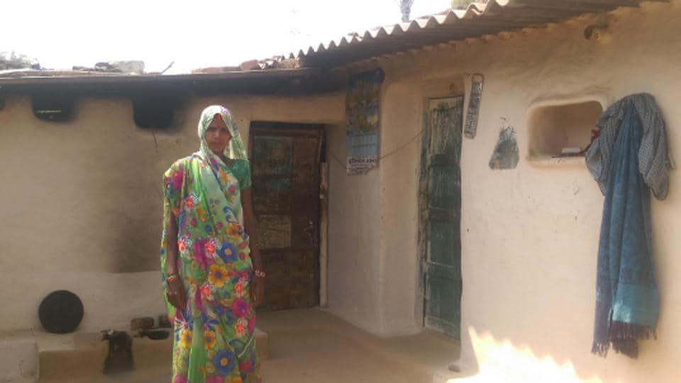 Homemaker Divya Devi outside her house–her solar panel visible on the roof–in Sonbhadra district, Uttar Pradesh (UP). Devi, like many others who live below poverty line in UP, was first promised a free electricity connection in 2005. Six months ago, Devi bought a small solar unit, which now powers two bulbs, enough for her four children to read past 6 pm and study harder.