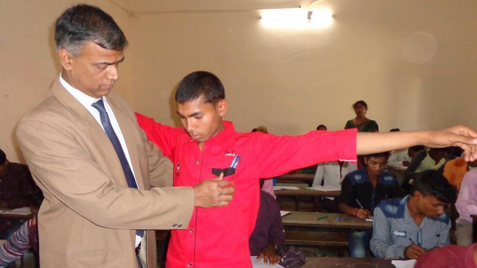 Patna divisional commissioner Anand Kishor checks an examinee at an examination centre in Patna.