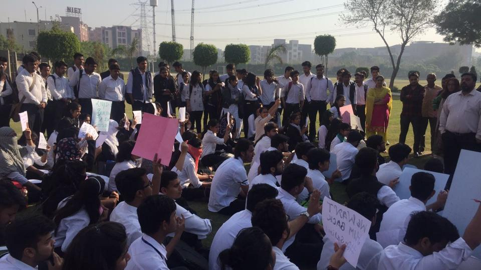 First-year students staged a sit-in on the college campus demanding the director's reinstatement.
