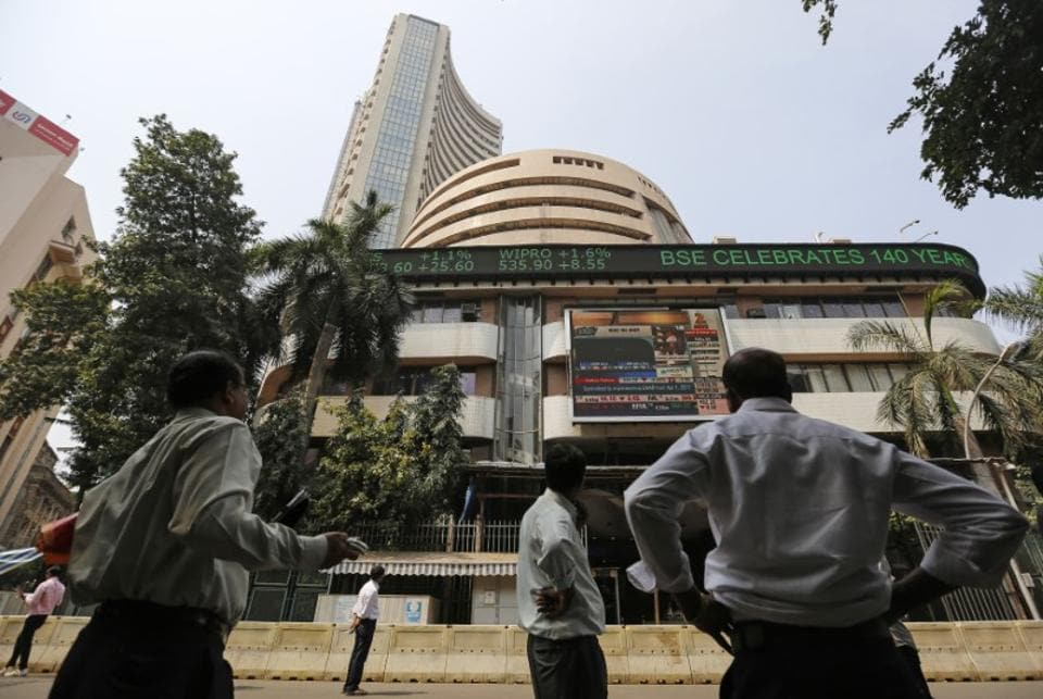 People look at a screen on a facade of the Bombay Stock Exchange (BSE) building in Mumbai