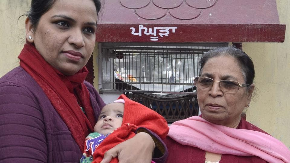 Venus Garg, chairperson of Red Cross Hospital Welfare wing and wife of DC Basant Garg, holding a girl child in front of a Pangoora in Amritsar on Wednesday.