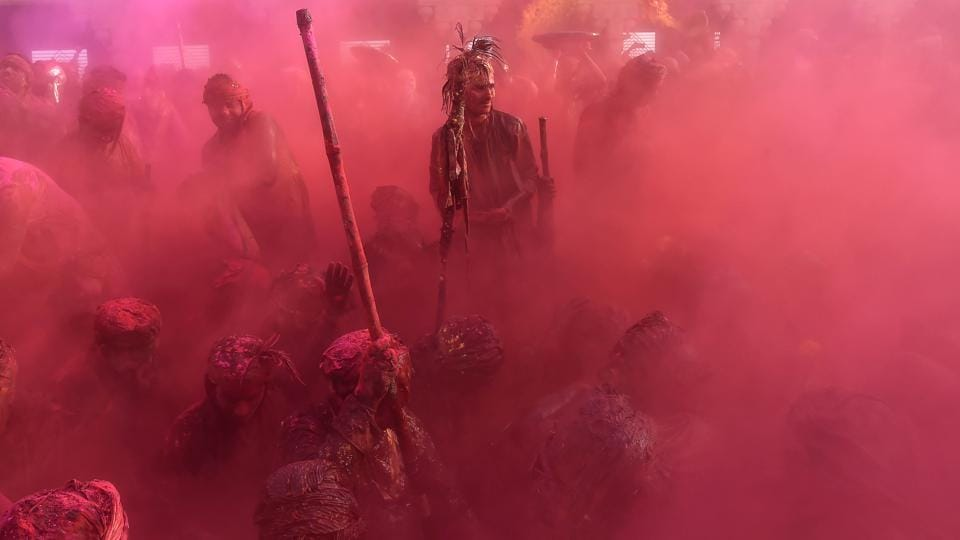 Indian villagers smear themselves with colours during the Lathmar Holi festival at the Nandji Temple in Nandgaon, some 120 kms from New Delhi. The women of Nandgaon, the home town of Hindu God Krishna, attack the men from Barsana, the legendary home town of Radha, consort of Hindu God Krishna, with wooden sticks in response to their efforts to put color on them, reciprocating acts performed yesterday in Barsana between the women of that village with the men of Nandgaon as they observe the Lathmar Holi festival.  (Ajay Aggarwal/HT PHOTO)