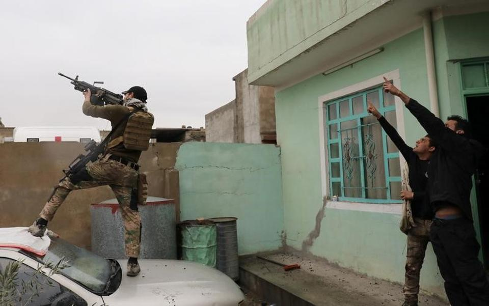 An Iraqi special forces soldier fires at a drone operated by Islamic State militants Islamic State militants in Mosul on March 4.