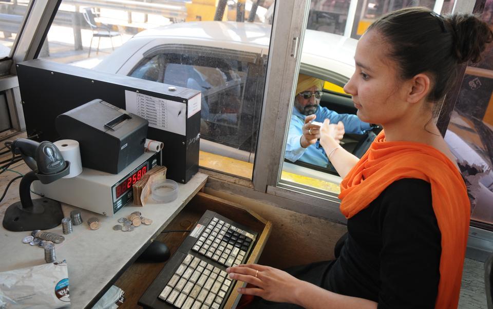 Toll attendant Manpreet Kaur giving cash receipt to a motorist.
