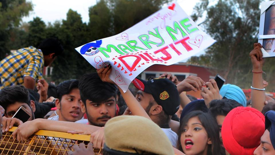A girl cheers on while she holds a 'Marry me Diljit' poster in the crowd. (Manoj Verma/HT Photo)